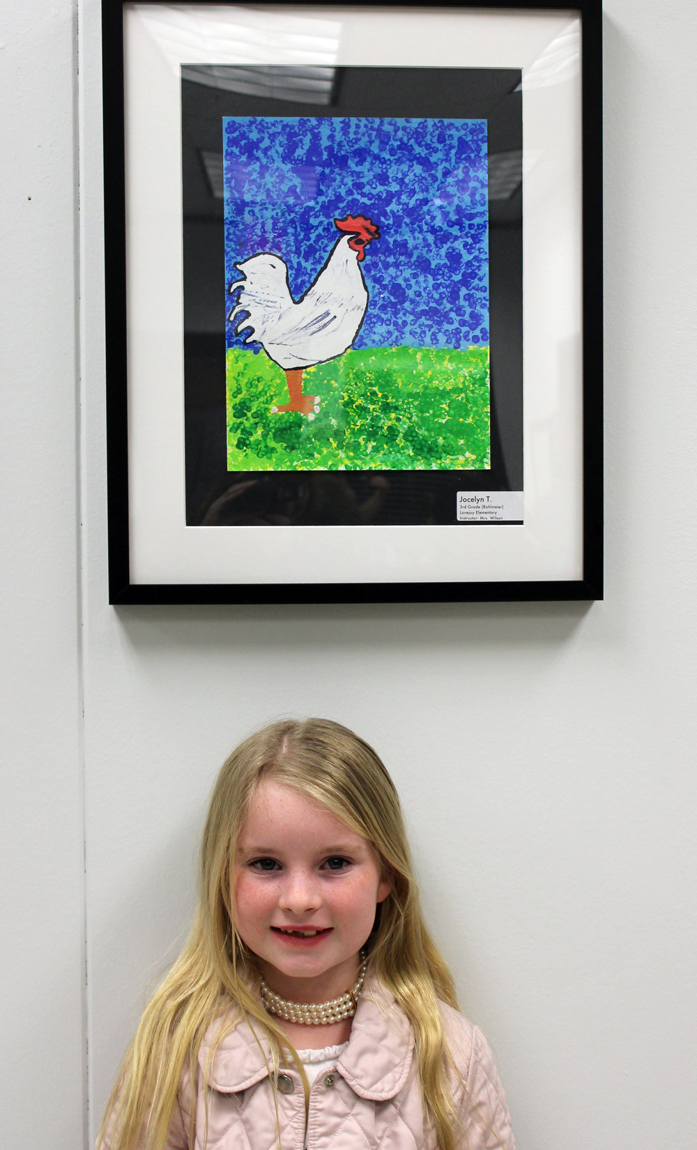 Lovejoy Elementary student, Jocelyn Tribuna, next to her artwork which she created using pointillism technique.