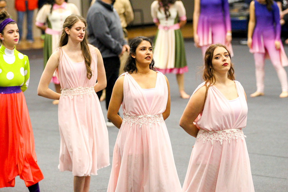Color Guard members Isabel Marsden, Riddhi Pareek, and Aubrey Huguley walk into the award ceremony.