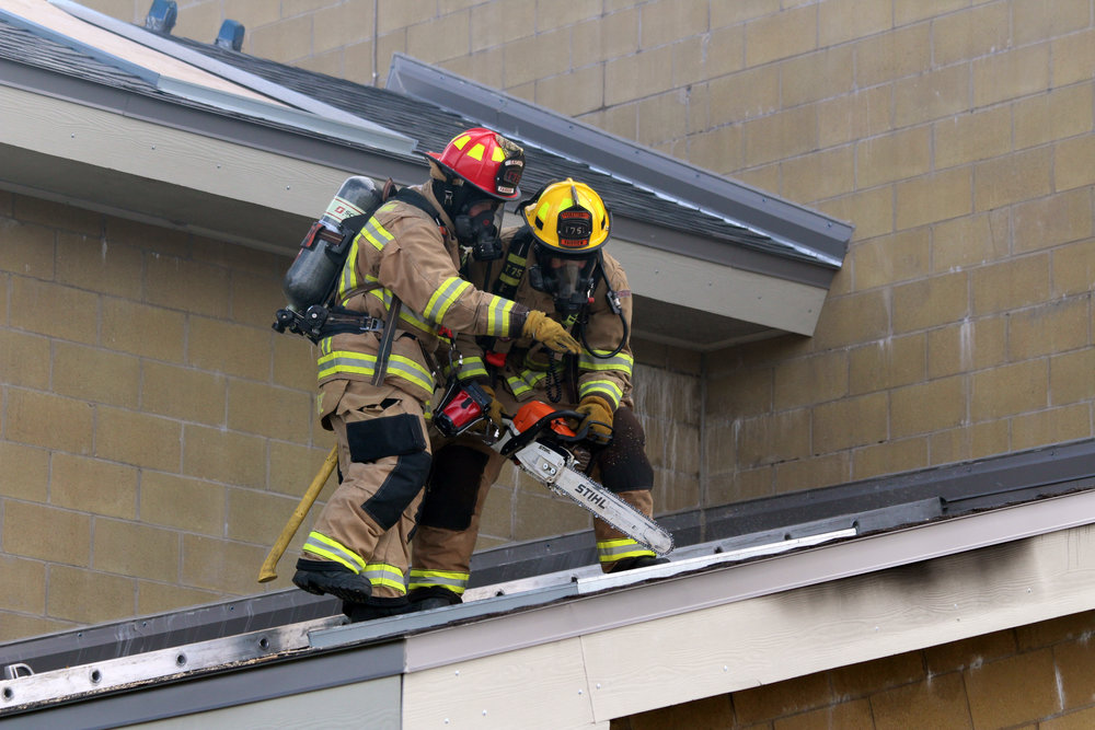 . Captain White and Firefighter Feig cutting a ventilation hole on the roof during a fire scenario. This assignment is always coordinated with the other interior fire crews.
