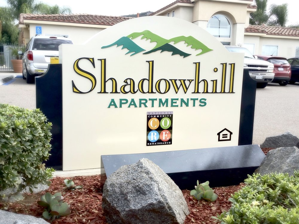 "Shadowhill Apartments monument sign is a refurbishing project in Santee, near San Diego. The aluminum letters and logo pieces were removed, sanded and repainted. The aluminum base cabinet was also completely sanded and repainted. New bright yellow vinyl details were applied to the ""Shadowhill"" letters… then the whole sign was carefully reassembled."