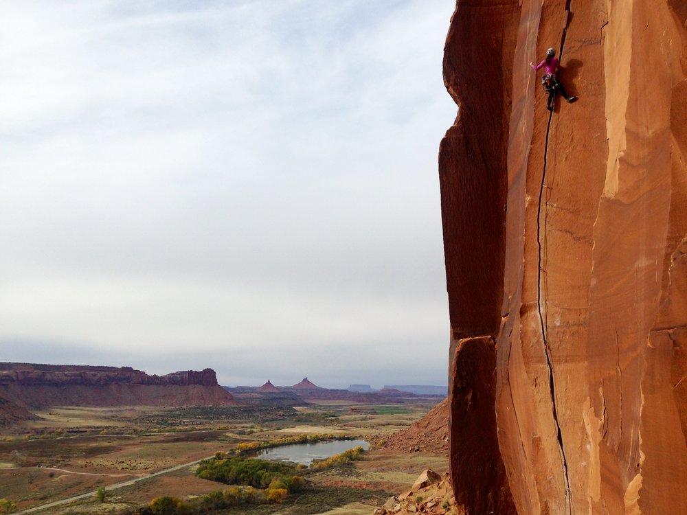 Erin climbing in Indian Creek, Utah, traditional territory of Navajo, Hopi, Zuni, Ute Mountain Ute, & Uintah Ouray Ute.