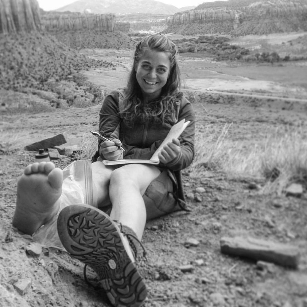 Erin sits in Indian Creek, traditional territory of the Navajo, Hopi, Zuni, Ute Mountain Ute, & Uintah Ouray Ute tribes, a few years ago nursing her freshly sprained ankle.
