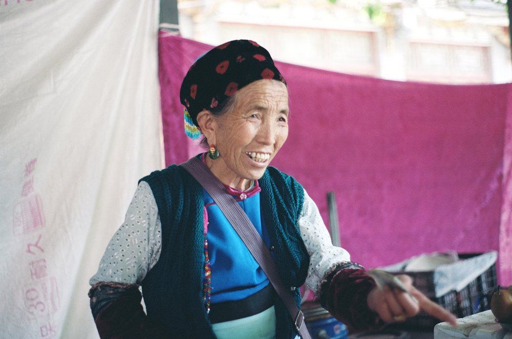 dali, yunnan. a bai fruit vendor at a local marketplace. she had just sold us some fresh mangosteen and grapes.