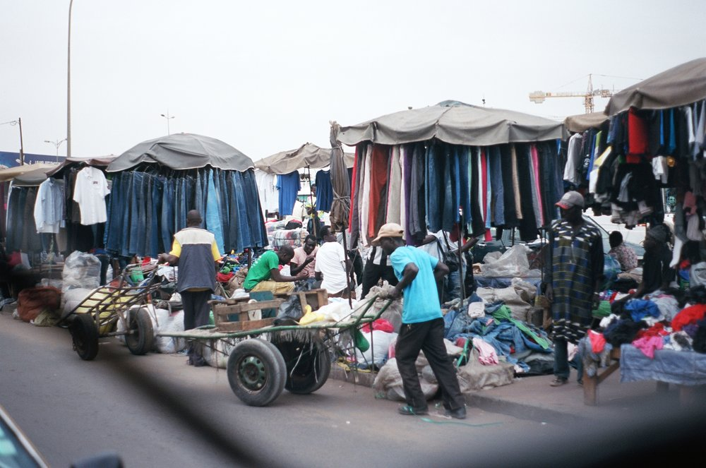 HLM, dakar. dozens of street vendors selling hundreds of articles of secondhand clothing on the side of a traffic-filled road.