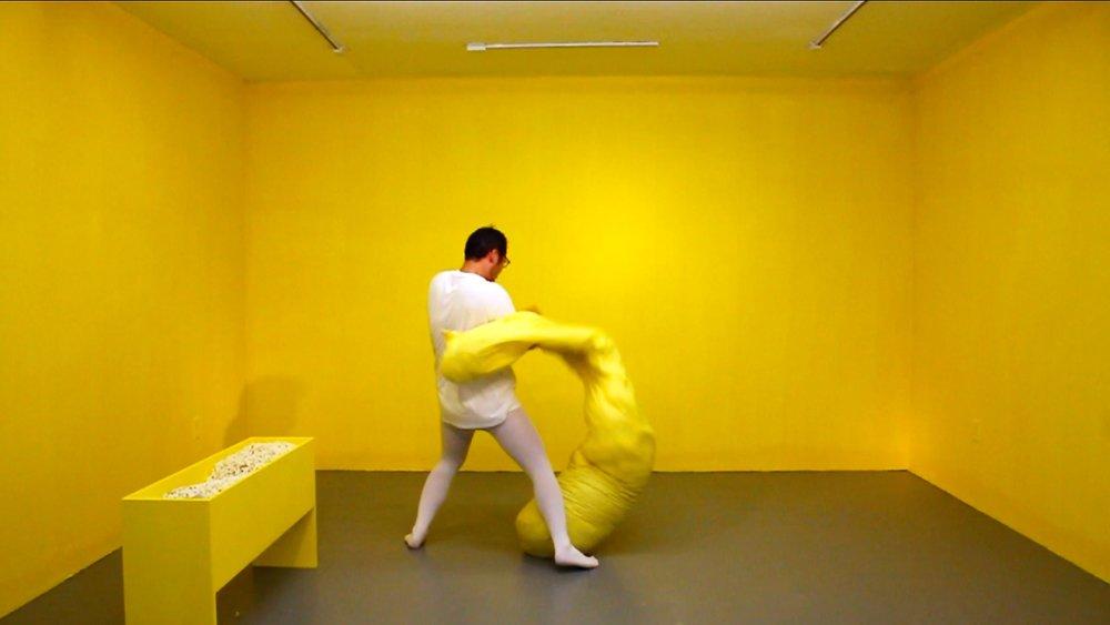Yellow  (video still) 2017. Artist, bean bag, popcorn. Dimension variable