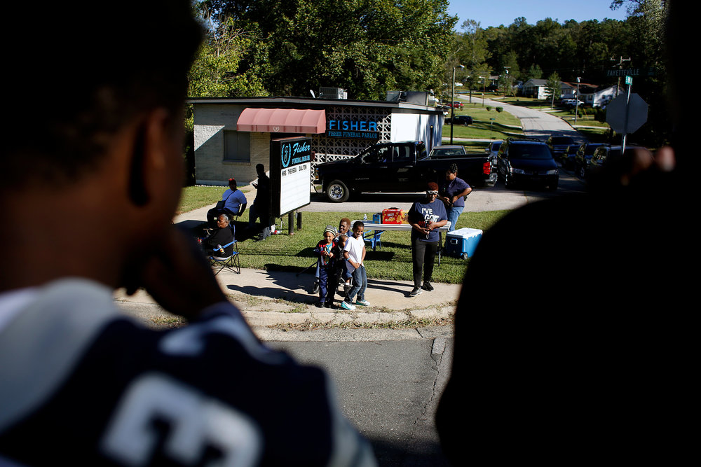 Hillside players shout to spectators from the back of a pickup truck during the school's annual homecoming parade, Sunday afternoon, Oct. 9, 2016, in Durham, N.C.
