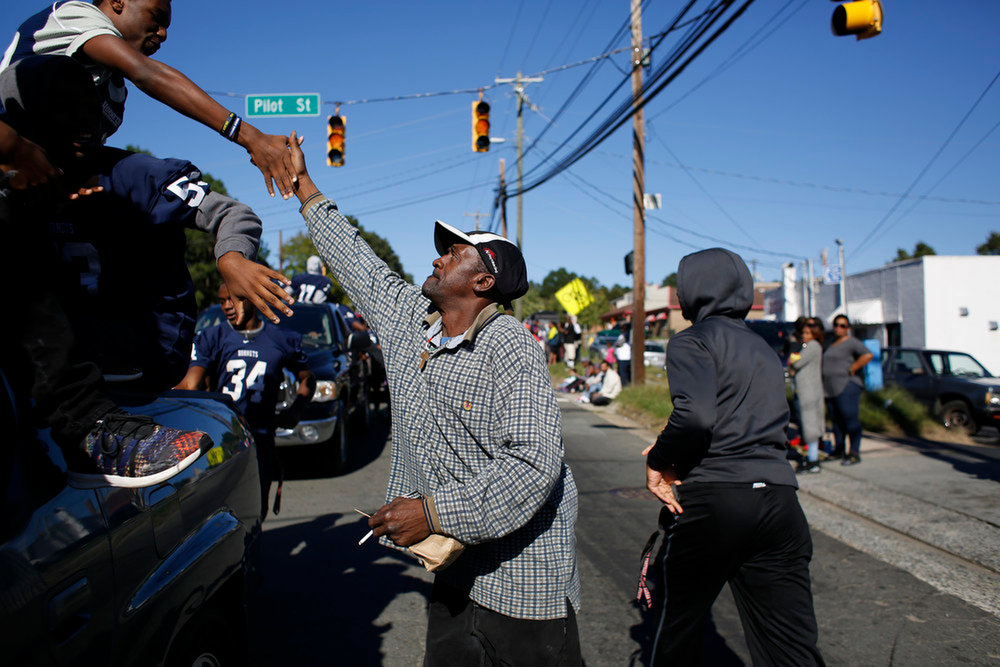 Hillside's Dymir Watson, left, slaps hands with a spectator during the school's annual homecoming parade, Sunday afternoon, Oct. 9, 2016, in Durham, N.C.