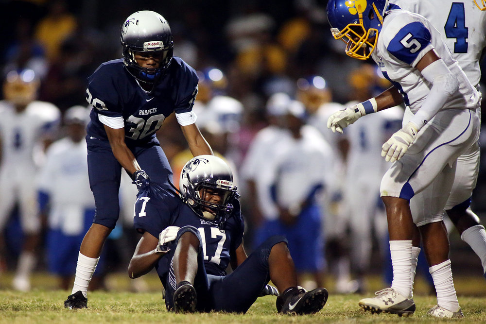 Hillside's Deshaun Mitchell, left, helps teammate Myles Dillon up off the ground after a play during a game against Dudley High School, Sept. 9, 2016, at Hillside High School. Hillside lost, 32-26, the team's only loss of the regular season.