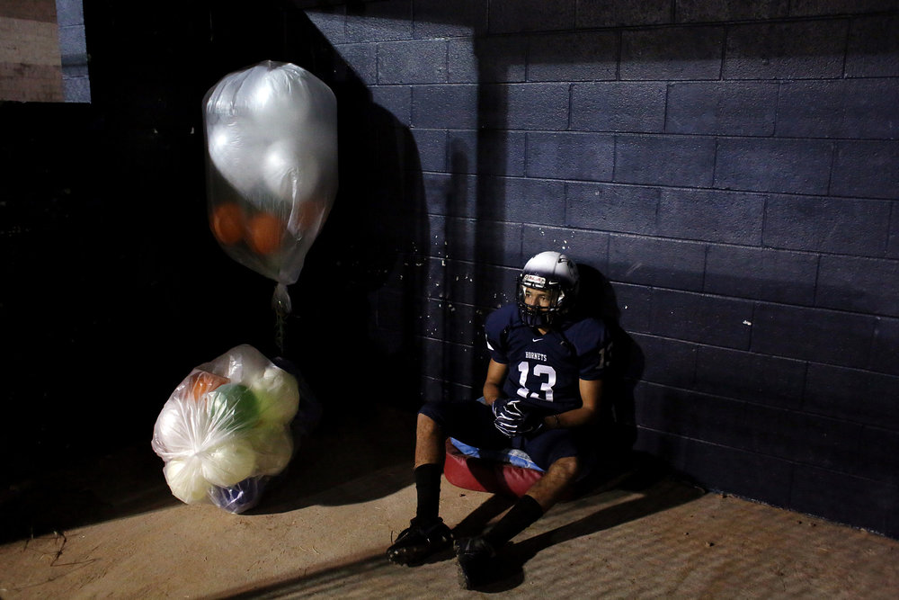 Hillside's Corey Spell sits alone in a baseball dugout during halftime of his team's last regular-season football game, which was played against Person High School, Nov. 4, 2016, at Hillside High School.