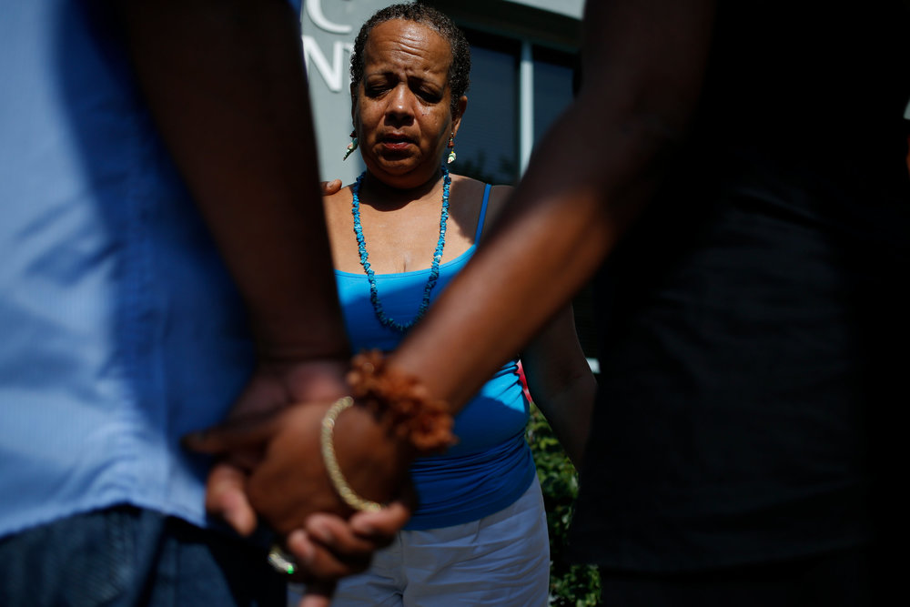 Mourners gather near the Emanuel African Methodist Episcopal Church, less than a day after Dylann Roof shot nine black churchgoers, Thursday, June 18, 2015, in Charleston, S.C.