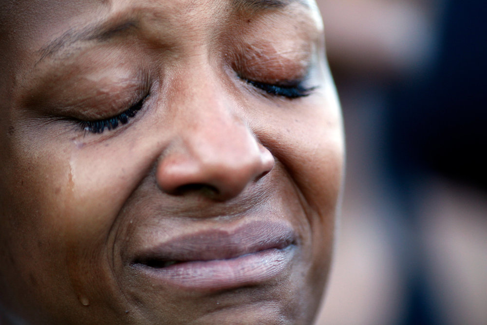 Tawana Clark, of Charleston, sheds a tear during a moment of silence at Bridge to Peace, a unity march in on the Arthur Ravenel Jr Bridge, June 21, 2015, four days after a shooting by Dylann Roof at the Emanuel African Methodist Episcopal Church left nine black churchgoers dead. She was one of thousands who participated in the bridge march; they started from either side of the bridge, which connects Mount Pleasant and Charleston, South Carolina, met in the middle and observed a moment of silence for those killed.