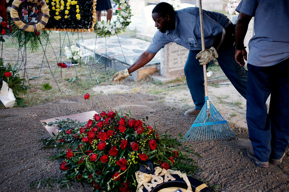 Bryan Williams tosses a rose onto the grave of state senator Clementa Pinckney, June 26, 2015, in Marion, S.C. Pinckney was one of nine churchgoers killed by Dylann Roof in a Charleston church.