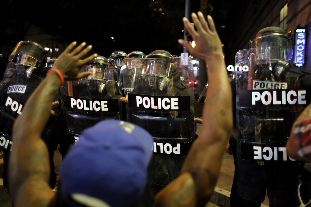 A protester raises his hands in front of a line of riot police, Sept. 21, 2016, at the intersection of North College and East Trade streets in downtown Charlotte, N.C.