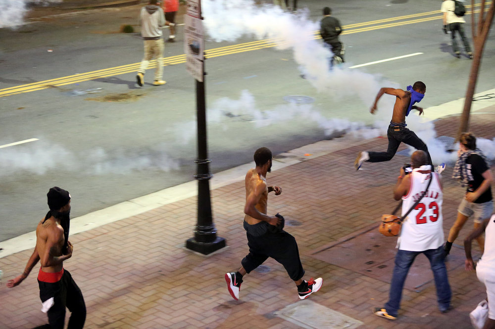 Protesters run from crowd control devices fired by riot police, Sept. 21, 2016, on East Trade Street in downtown Charlotte, North Carolina.