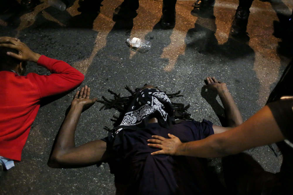 Protesters lie on the street in front of a line of riot police officers, Sept. 21, 2016, at the intersection of North College and East Trade streets in downtown Charlotte, N.C.