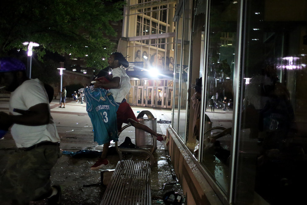 A man carrying basketball jerseys and a basketball jumps out of the broken window of the looted Charlotte Hornets team store, Sept. 21, 2016, off of East Trade Street in downtown Charlotte, North Carolina.