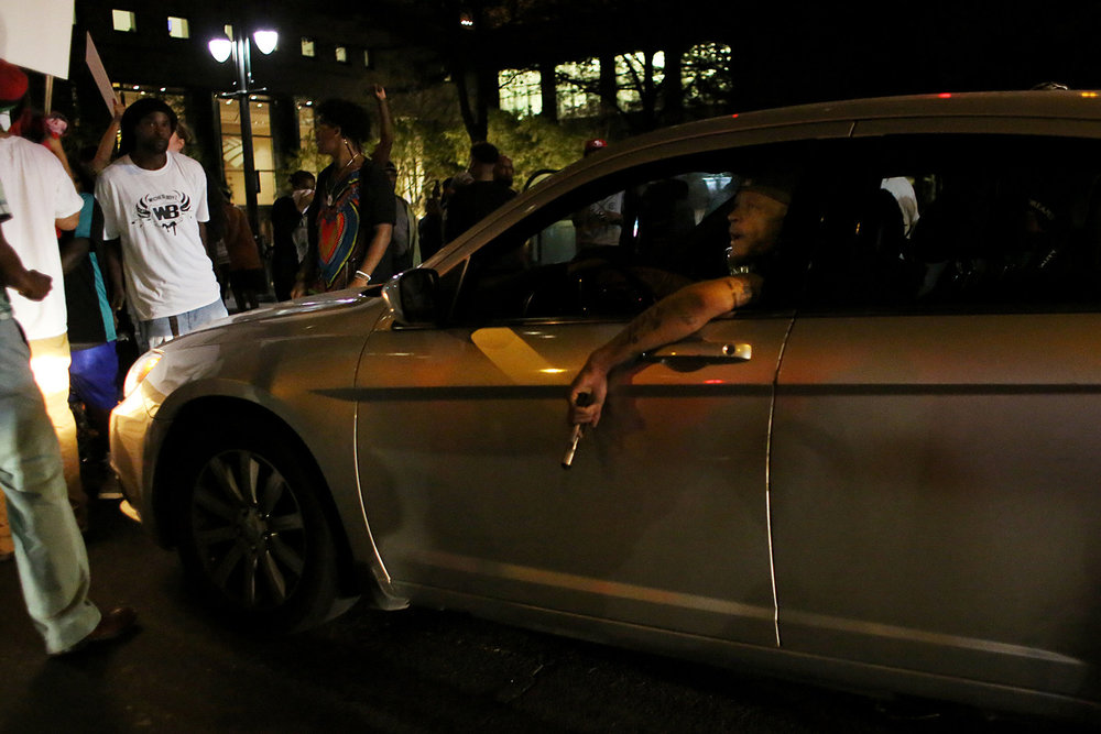 A man in a car brandishes a handgun during a confrontation with protesters who were blocking traffic, Sept. 21, 2016, at the intersection of North College and East Trade streets in downtown Charlotte, N.C.