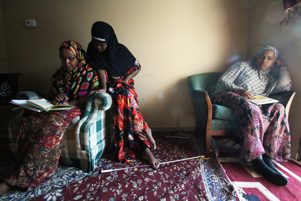 "Fadumo helps her aunt and guardian ""Big Fadumo"" Kalif read a children's book in their apartment."