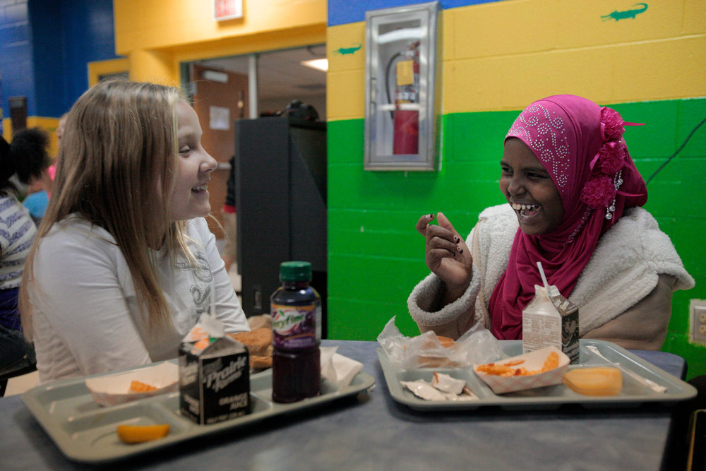 Fadumo Farah Abdi and her friend, Emily Hope, share a laugh during lunchtime at Bend Gate Elementary School.