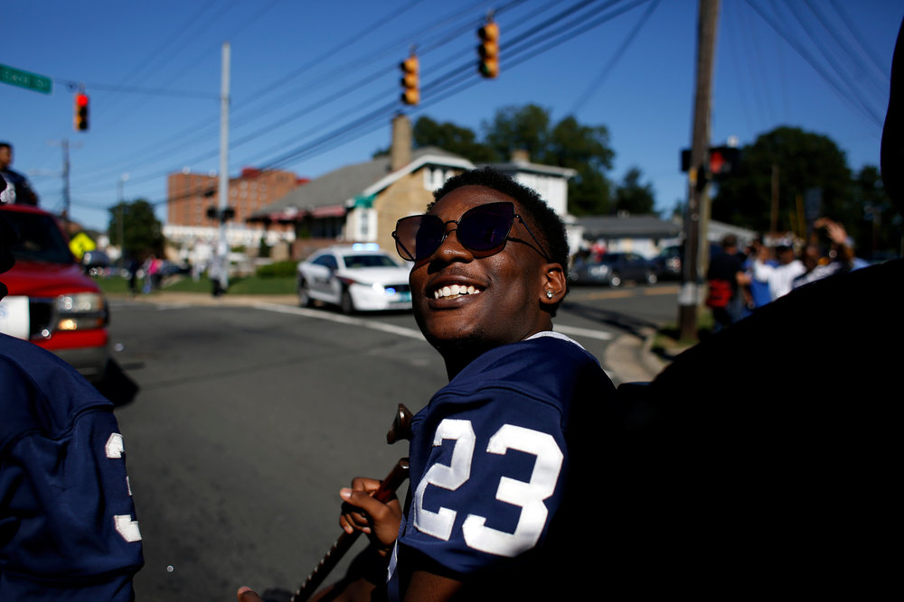 Hillside High School's Bakari Lee looks up at teammates after receiving a pair of sunglasses from a stranger watching the school's annual homecoming parade, Sunday afternoon, Oct. 9, 2016, in Durham, N.C. The parade wound its way down Fayetteville Street, from East Lawson Street to the high school.