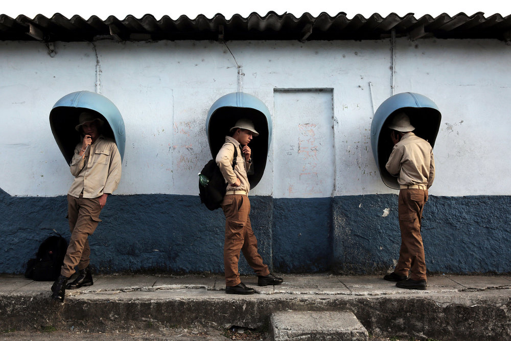 Young Cuban men use payphones March 10, 2017 in the Regla municipality of Havana, Cuba. The young men are part of Ejercito Juvenil del Trabajo -- the Youth Labor Army -- which works on a range of domestic projects, from agricultural and construction work to mosquito eradication.