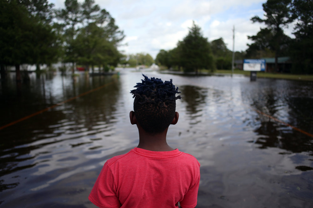 Tyrese Jordan, 11, looks back toward a dry section of roadway, Sept. 17, 2018, on Highway 41 in Trenton, N.C., as he waited for Russell Jordan to return from their flooded home. They were attempting to evacuate their family's dog, which was stuck on sliver of dry land, but the water was too high near their home. After evacuating their home, the family was bounced to several different shelters, with each one progressively further from home.