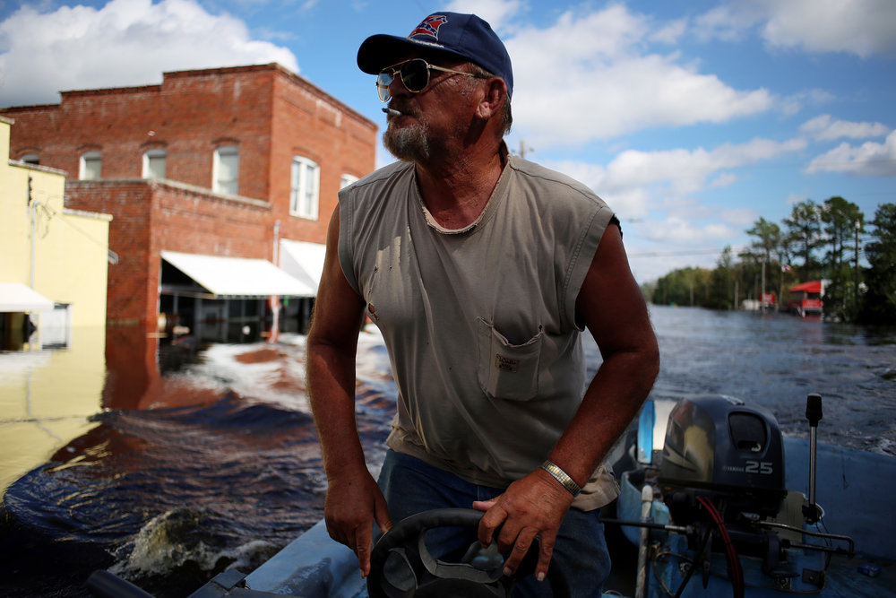 """Donald Jones, of New Bern, guns his boat down Main Street, which was flooded by the nearby Trent River, Sept. 18, in Pollocksville, N.C. Jones was helping deliver food and water for Kim Arthur, whose home was in an area largely cut off from outside resources. """"I'm about 10 minutes out in the country and this is the only way to get to town,"""" she said."""