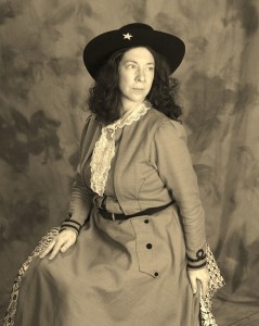 "Annie Oakley PORTRAYED BY KIM HANLEY - Annie Oakley, born Phoebe Ann Mosey, was probably the most famous woman of her day. With photographs and posters everywhere, she and professional partner Buffalo Bill Cody may have been the first international superstars. The diminutive sharpshooter and exhibition shooter, who made her own costume, competed in a sport and in a world dominated by men. The no-holds-barred performer learned to shoot from practical necessity, hunting to feed her parents and siblings. Growing up poor, overcoming a difficult and even abusive childhood, she just did what she needed to do to survive and to keep her family going.She fought for safe working conditions, fair and equal pay for a days work regardless of gender or heritage, and for a first-rate show that presented good solid family entertainment. International fame and success came with a price. Later in life she had to fight to maintain the honor of her name. Yet she steadfastly supported the country in times of war, and put many young girls through school at her own expense. Believing that women were just as capable as men, she firmly insisted that they should strive to achieve any goal or occupation that interested them. Her motto was to ""Aim for a high mark…for practice will make you perfect."" and her hope was that all women would reach the ""Bulls-eye of Success.""Kim Hanley clears up any and all Annie Get Your Gun misconceptions. Ms. Hanley is passionate about Oakley, eager to share Annie's inspiring life story, a life much more interesting than the myths that have grown up around her. Like Oakley, Hanley has created her own costume, can ride and shoot and has done some archery. And like Oakley, Hanley is committed to her family, to education, and to philanthropic causes. Audience members learn from experience that perseverance overcomes obstacles. Volunteers toss red bean bags into a basket, first with their dominant hand and then with their other hand, then over their shoulder, then when the basket is moving. Their skills improve with practice and they learn they will continue to succeed even as the difficulty of their task increases.  Ms. Hanley's Annie Oakley is a perservering dynamo whose spirit is contagious."
