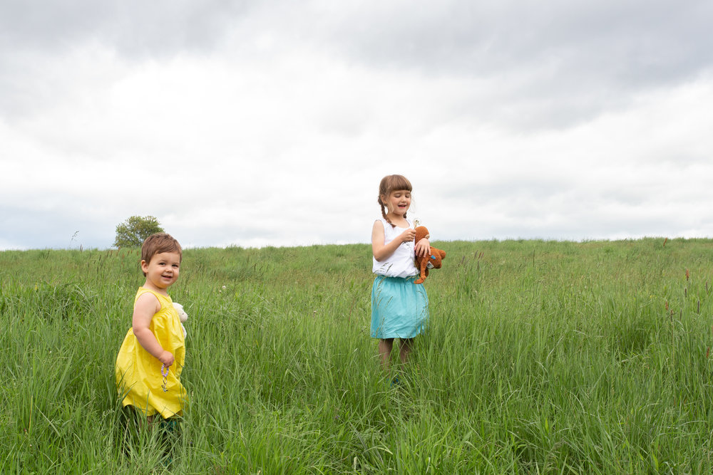 Two sisters laughing in a field in Germantown, NY.Photograph by Laughing Heart Photography.