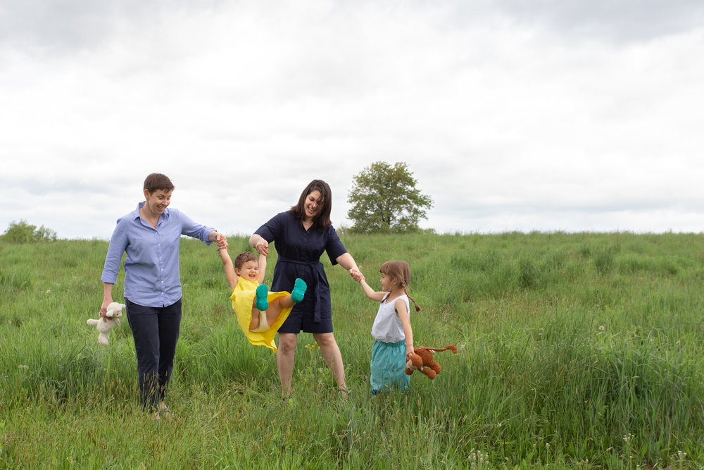 Two moms and their daughters in a field in Germantown, NY.Photograph by Laughing Heart Photography.