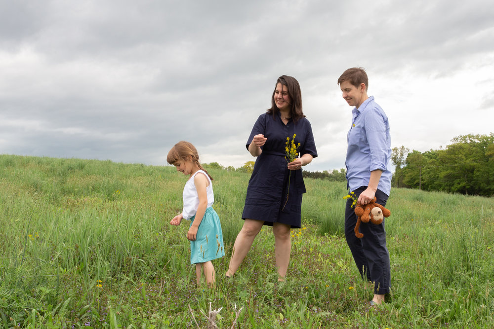 Two moms and their daughter in a field in Germantown, NY.Photograph by Laughing Heart Photography.