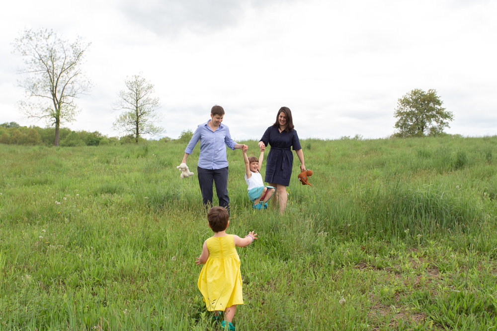 Two moms with their daughters in a field in Germantown, NY.Photograph by Laughing Heart Photography.