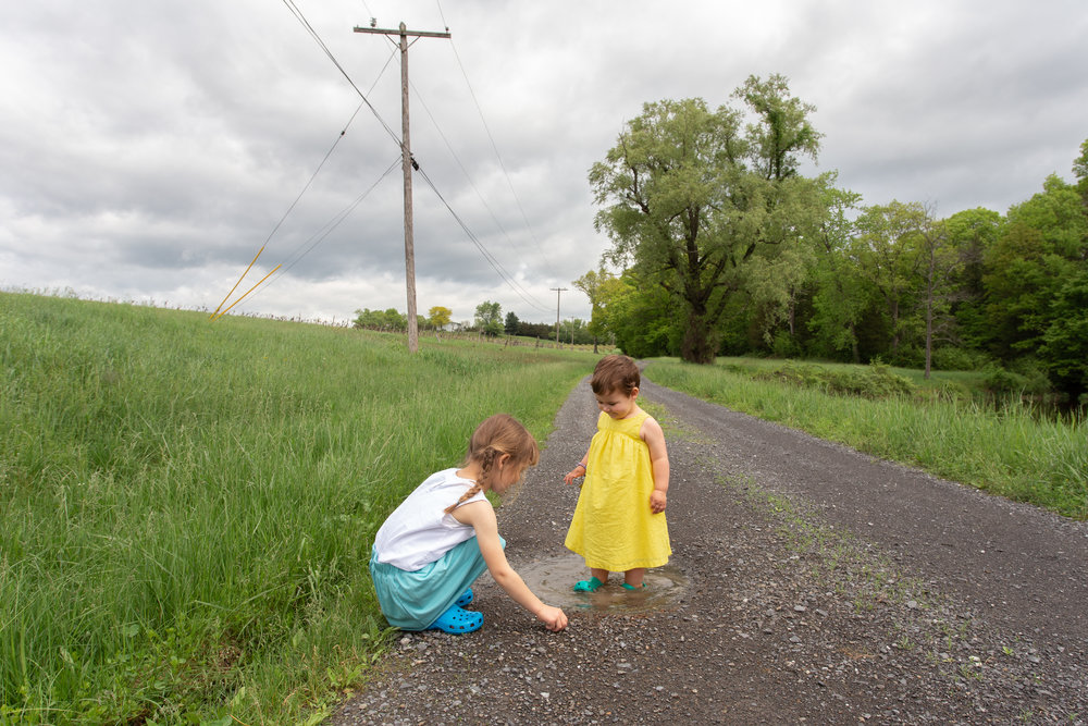 Two sisters on a dirt road playing in a puddle in Germantown, NY.Photograph by Laughing Heart Photography.