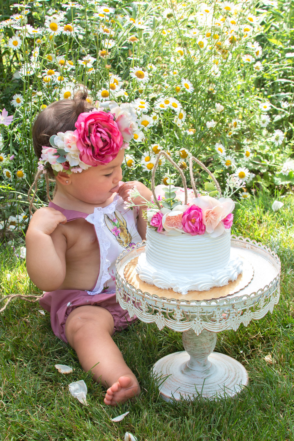 Birthday girl with flower crown sitting with a cake in Ringwood, New Jersey Botanical Garden.Photograph by Laughing Heart Photography.