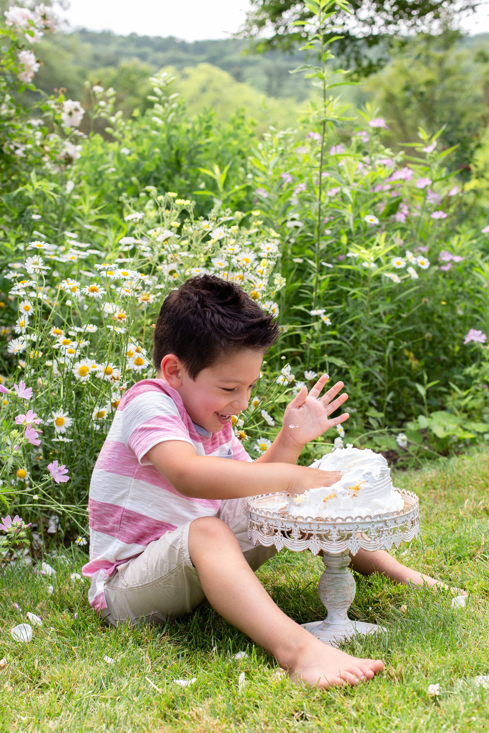 Big brother smashing a cake in Ringwood, New Jersey Botanical Garden.Photograph by Laughing Heart Photography.
