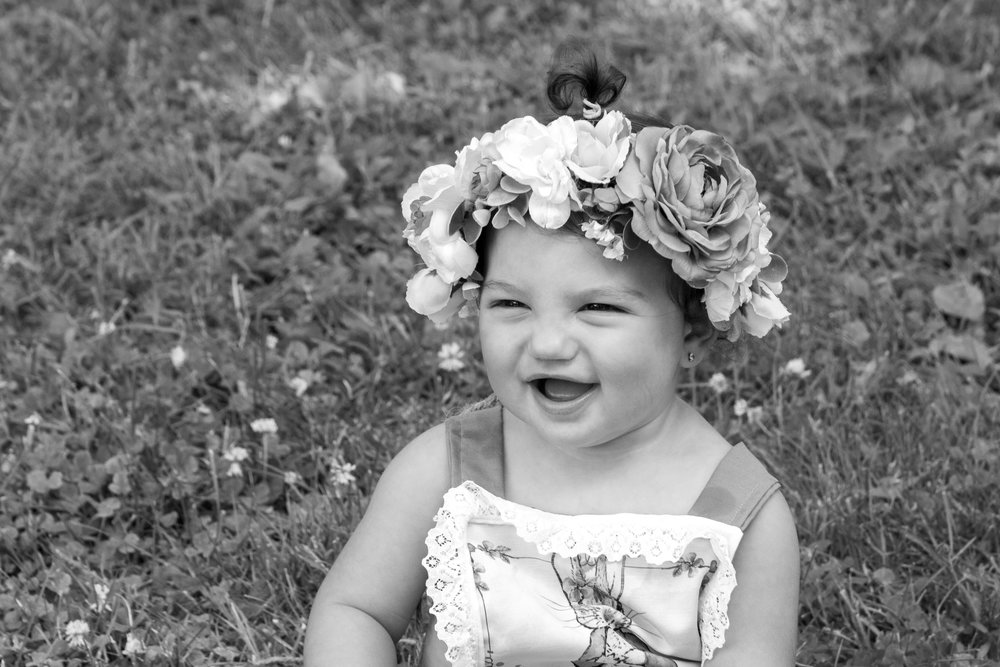 Birthday girl with flower crown laughing in Ringwood, New Jersey Botanical Garden.Photograph by Laughing Heart Photography.