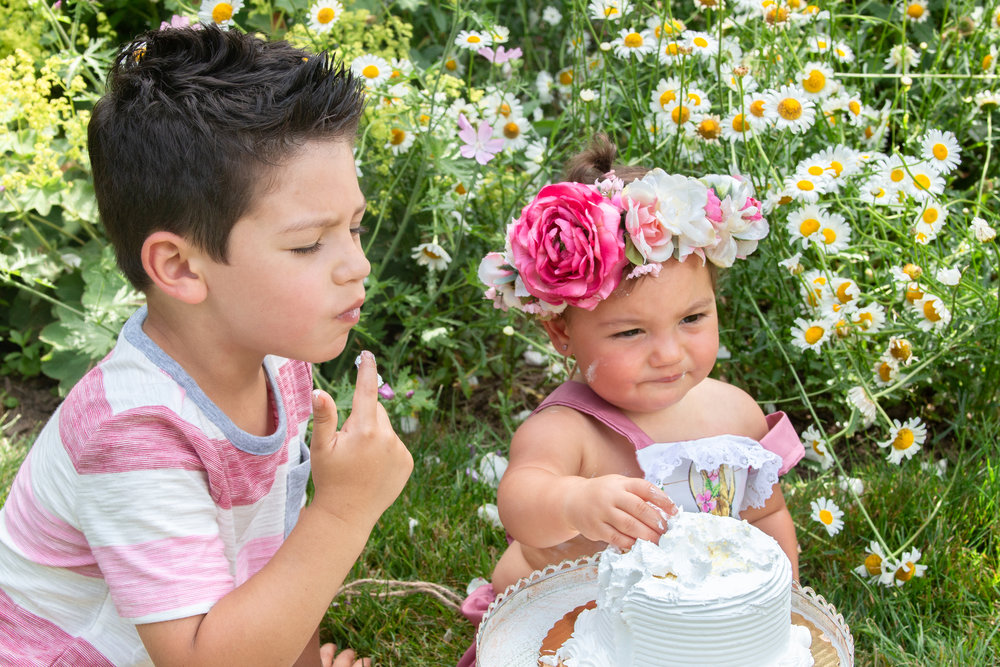 Big brother and birthday girl with flower crown tasting a cake in Ringwood, New Jersey Botanical Garden.Photograph by Laughing Heart Photography.