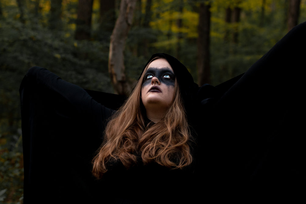 Woman dressed in all black in woods of Hewitt, NJ. Photo taken by Laughing Heart Photography.