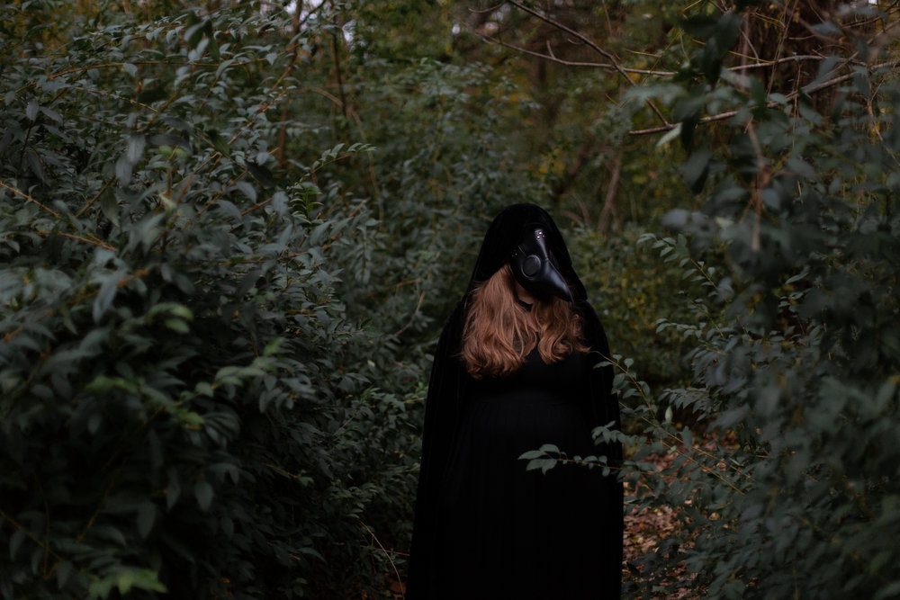 Woman dressed in all black with a long nose mask in woods of Hewitt, NJ. Photo taken by Laughing Heart Photography.