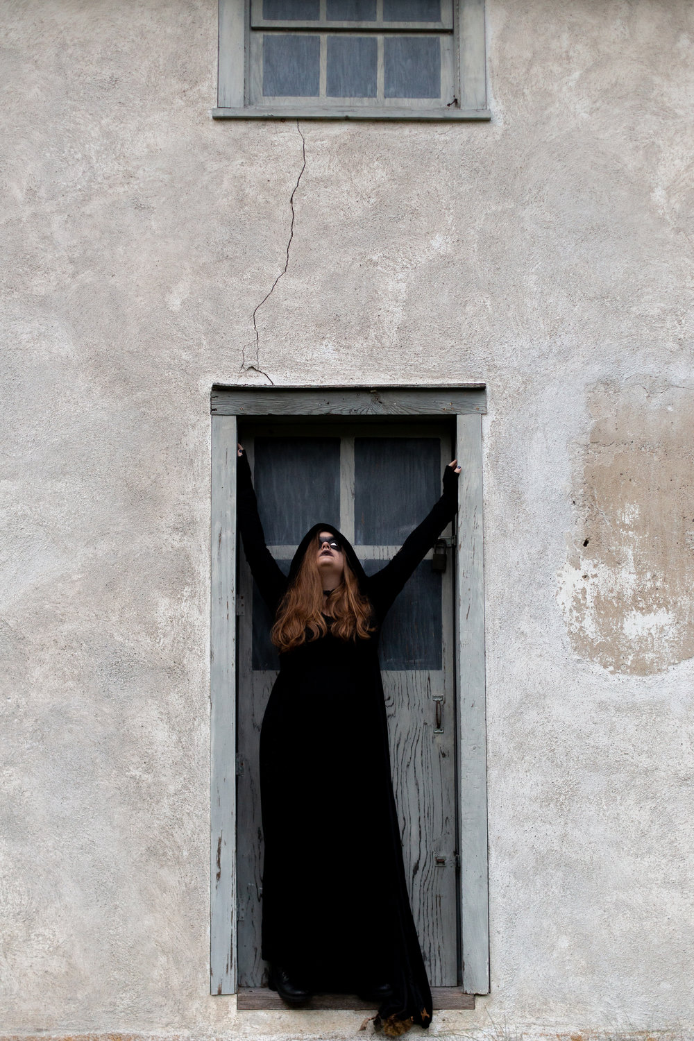 Woman dressed in all black standing in a doorway in Hewitt, NJ. Photo taken by Laughing Heart Photography.