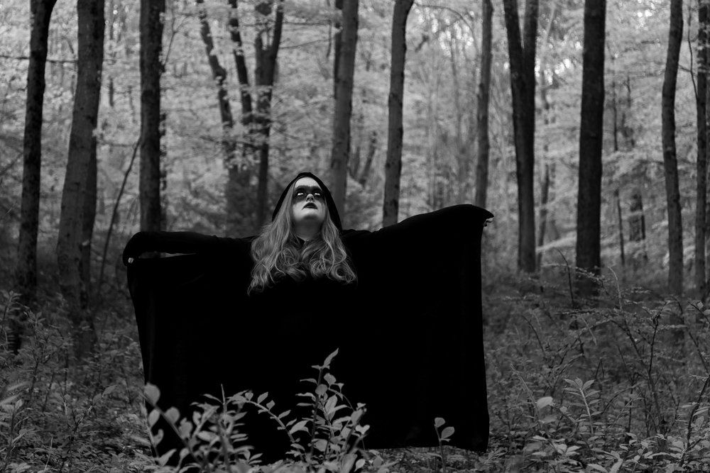 Woman wearing all black standing in the woods of Hewitt, NJ. Photo by Laughing Heart Photography.