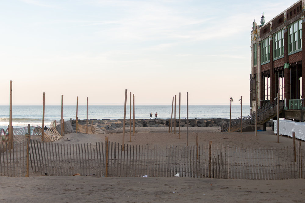 Two people walking along rocks on Asbury Park Beach in New Jersey. Photo by Kayleigh Ann Archbold.