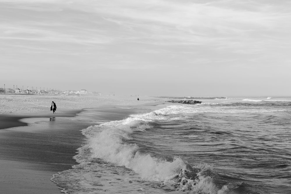Woman walking along beach in Asbury Park, New Jersey. Photo by Kayleigh Ann Archbold.
