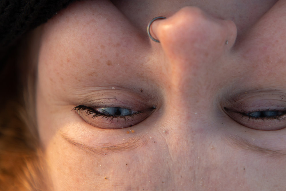 Sand in woman's eye in Asbury Park, New Jersey. Photo by Kayleigh Ann Archbold.