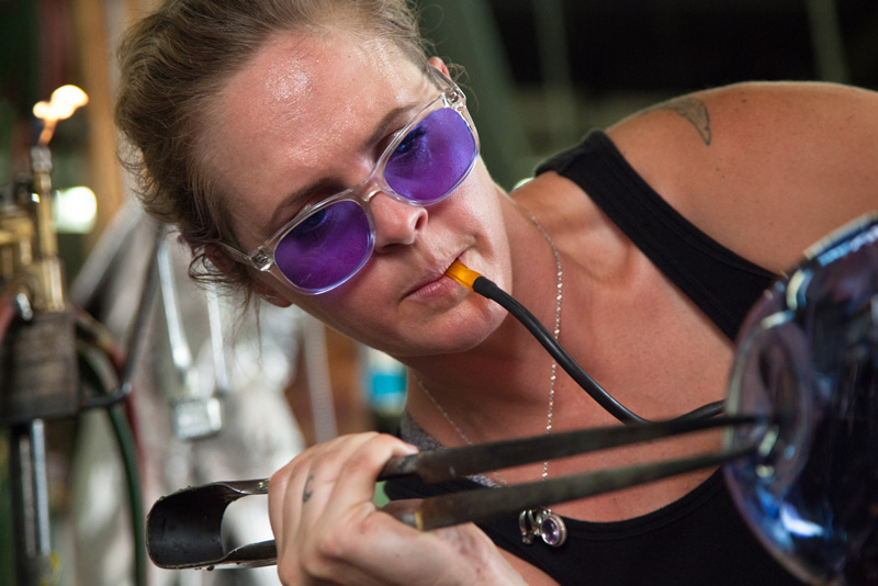 Tara using jacks to shape the glass while blowing into the pipe. Photo credit: Terminal City Glass Co-op