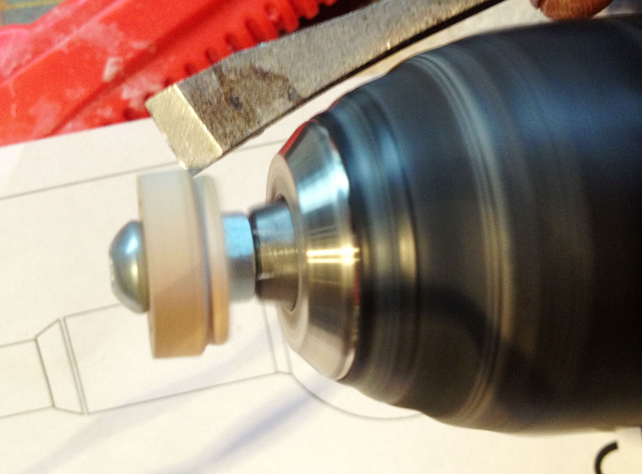 """After chucking it to my hand drill, I used a chisel as a """"poor man's lathe"""" to shape the piece. Here I've just cut the parts that inserts into the upper arm pipe."""