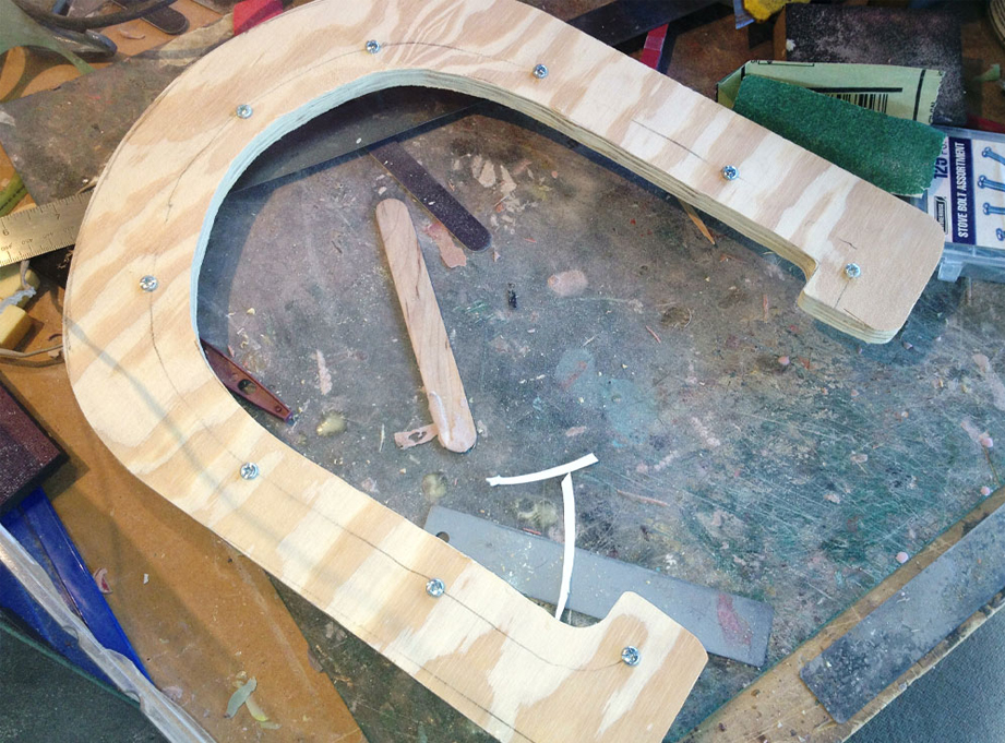 I cut two pieces of 1/4″ plywood to make a parting line for the mother mold. This was placed over the center of the helmet and Plasti-Paste II was applied on each side to support the mold rubber.