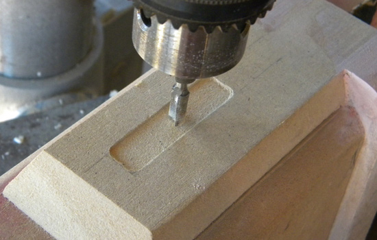 I chucked a router bit into drill press and carved out a decorative panel in the top.