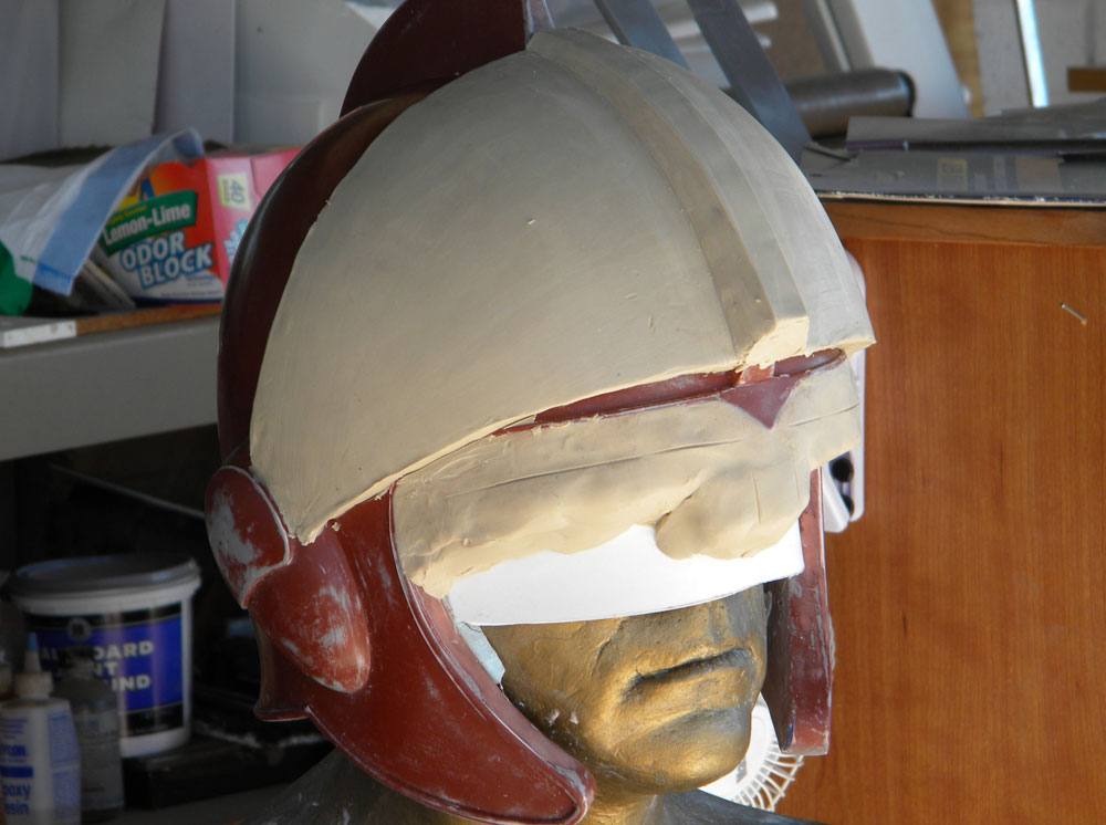 To make the visor, I placed the helmet master back on my plaster head and sculpted the visor lens as smoothly as I could.