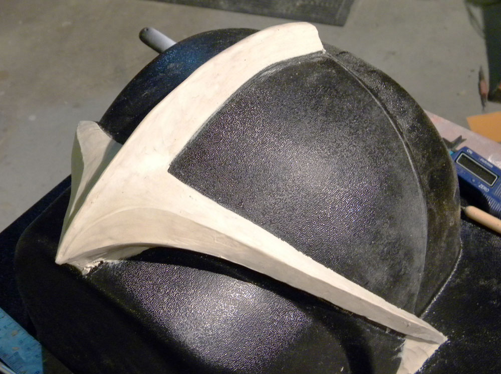 When I had the clear visor pulled, I also had them make an ABS copy that I could use as a sculpting form for the visor trim. I used clay to shape the visor and got it as smooth as I could (which isn't very smooth, as you can see)